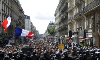 Protestors march waving French flags during a demonstration in Paris, France