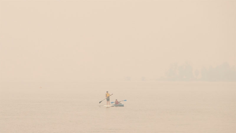 Wildfire smoke fills the air and obstructs the view of the mountains as people continue to take part in outdoor activities