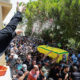 A woman throws rice as mourners carry the coffin of Hezbollah member Ali Shibli